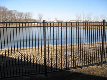 Black basic steel fencing are installed around a small pond to minimize water hazards.